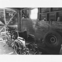 Image of UNRS-P2003-13-357 - Photograph of two wheel chairs and a tire in a cattle shed, Capurro Ranch, Yerington.