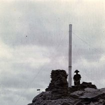 Image of UNRS-P2004-18-186 - Photograph of man standing next to gauge with rocks.