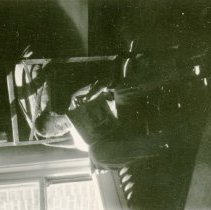 Image of UNRA-P3376-138 - Photograph of Student reading near window in Lincoln Hall Room 208. Photos numbered 100 through 161 were removed from a student's WWII era album; original order was maintained.