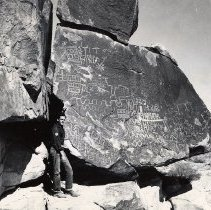 Image of UNRS-P1721-1 - Photograph of man standing by petroglyphs in Clark County. Handwritten on verso: Petroglyphs abound in Clark County. Clark Co. petroglyphs.