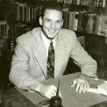Image of UNRA-P3628-00230 - Photograph of Coach Hugh Smithwick seated at desk. 1954.