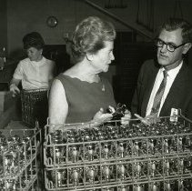 Image of UNRS-P1993-03-0125 - Eva Adams, director of the mint.  John S. Millar, Purchasing manager, Schlage Lock Company.  In background-Tessie Schembri.  Photographed in the Lacquer Department, Schlage Lock Company. Taken at the Schlage Lock Company.  Miss Adams received at that time the honorary degree of Master of Kleidology.  August 24, 1967. Photo by Mary A. Danforth, Schlage Lock Company.