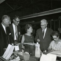 Image of UNRS-P1993-03-0127 - David T. Marvel, Vice President, Olin Brass Metals Division.  John S. Millar, Purchasing Manager, Schlage Lock Company.  Eva Adams, Director of the Mint.  Ernest L. Schlage, Vice President and Director of Research, Schlage Lock Company.  Alexandra Bobroff (Key Assembly) photographed in the Key Room, Schlage Lock Company. Taken at the Schlage Lock Company.  Miss Adams received at that time the honorary degree of Master of Kleidology.  August 24, 1967. Photo by Mary A. Danforth, Schlage Lock Company.