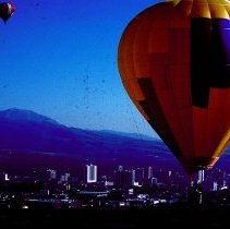 Image of UNRA-P3459-120 - Photograph of two balloons, with downtown Reno and mountains in the background during the Reno Balloon Races of 1990 at Rancho San Rafael Park.