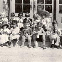 Image of UNRA-P1749-0380 - Nutrition: Unidentified Las Vegas kindergarten children sitting on steps drinking milk (1926)