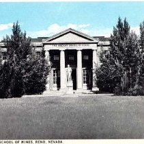 Image of UNRS-P1992-03-1348 - Image of the center of the front of Mackay School of Mines and statue as seen through rows of trees on the quad. Caption on image front: The Mackay School of Mines, Reno, Nevada. Circa 1920.