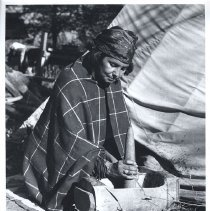 Image of UNRS-P1997-50-0468 - [Gathering camas at Kamiah, near Nez Perce Reservation, Idaho, 1961.] 5. The dried camas bulbs are pounded in a mortar into a flour that is then baked to bread.