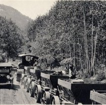 Image of UNRS-P2003-02-004 - Photograph of Mineco Transportation Co. CLB Track Layer tractor pulling ore wagons, as seen from the rear, with an automobile passing in opposite direction on Cardiff Lane near Big Cottonwood Canyon, Utah, July 1916. Handwritten on verso: On Cardiff Lane. July 1916. J. D. Gillen, RD #5, Murray, Utah, Box 31.