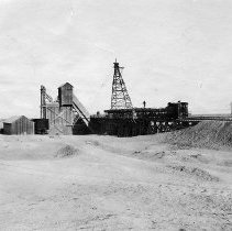 Image of UNRS-P2008-18-2034 - [B_W photos- Lahontan Dam Construction]. Cement plant at left, cableway head tower in center. Gravel train dumping into bins over belt conveyor. November 30, 1912.
