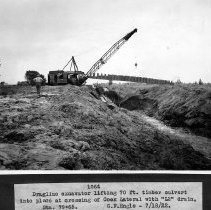 """Image of UNRS-P2008-18-3904 - Dragline excavator lifting 70 ft. culvert into place at crossing of Cook Lateral with """"L2"""" drain, Sta. 79+65. G.F. Engle, July 18, 1922."""