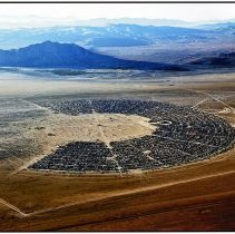 Image of UNRS-P2014-02-00019 - Aerial photograph of Black Rock City during Burning Man. Color print.