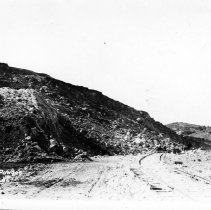 Image of UNRS-P2564-1 - Photograph of blasting done for copper mining in Ruth Nevada, showing railroad bed.