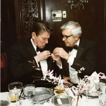 Image of UNRS-P2015-12-00148 - Senator Laxalt helping President Reagan pin something to his lapel at the Lamb Fry: scrapbook 13, page 70, box 931