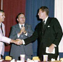 Image of UNRS-P2015-12-00190 - Ronald Reagan and  Senator Laxalt shaking hands while Senator Jesse Helms and two other men clap at the 1976 Republican National Convention in Kansas City, Missouri: scrapbook 10, page 19, box 854