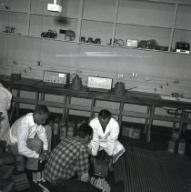 Image of UNRA-P110-086 - Photograph of three unidentified men assembling equipment (1963)