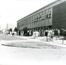 Image of UNRA-P158-02 - Registration at the Gymnasium: students walking outside Gymnasium (1956)
