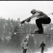Image of UNRA-P1583-24 - Unidentified male skier in the air, with two observers below (1959)