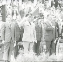 Image of UNRA-P2-010 - Photograph of Governor's Day: Governor Grant Sawyer and other dignitaries saluting, with audience in bleachers in background (1962)