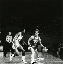 Image of UNRA-P1512-084A - Basketball: UNR vs. Cal State fullerton game. Caption: Dribbling at its best (1985)