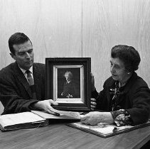 Image of UNRA-P437-04 - Effie Mona Mack and David Heron, Library Director, sitting beside portrait of Mark Twain. (ca. 1962)
