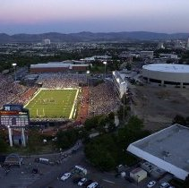 Image of UNRA-P3387-0017 - Mackay Stadium, first night game, north looking south, from scoreboard, city view in background.