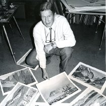 Image of UNRA-P3426-0040 - Craig Sheppard kneeling before six of his Western paintings spread on the floor in the foreground (early 1970s?)