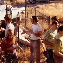 Image of UNRA-P3427-1268 - 9 unidentified students at a chain-link fence near parked cars (1971).