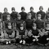 """Image of UNRA-P3432-3 - Photograph of University of Nevada football team at Mackay Stadium (Historic). Back row: Coach Courtright, third from left: Quarterback Willis Church; 6th from left: Herb Foster, Right Halfback; far right: Assistant Coach Williams; Middle row, from left: Max Charles; 4th from left: Otis Wright, Paul Harwood; 7th from left: Ted Fairchild, Left End; William Martin, Right End and Captain Elect; front row, 3rd from left: """"Tiny"""" Mahlon Fairchild, Right Guard and Captain of the 1920 Varsity (Fall 1920)"""