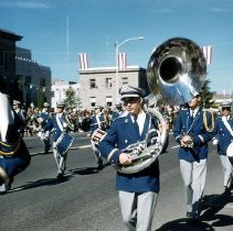 Image of UNRA-P3475-0304 - Photograph of Fred Dugger with Sousaphone, marching with unidentified members of the University of Nevada Marching Band in Carson City during the Nevada Day parade.