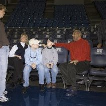 Image of UNRA-P3528-11 - Unidentified woman and donor Luther Mack standing near Athletic Director Cary Groth, two boys, and actor Bill Cosby in the Lawlor Events Center arena (February 16, 2007)