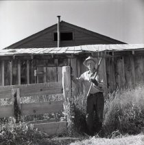 Image of UNRS-P1985-08-26671 - Folder 197. [Jack Whitehead standing next to fence with pitchfork on shoulder. (Print is cropped.)] Thirty-six negatives total: Jack Whitehead Ranch [on Franktown Road]; Haying Time; 1971 (neg. 2x2)