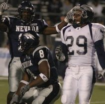 Image of UNRA-P3608-D006-S01-00021 - Photograph of Wolf Pack players #31, 18, and 47 in a pile-up with two Rice players