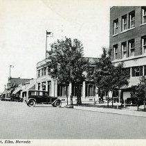 Image of UNRS-P2017-01-00018 - Caption on image: Railroad Street, Elko Nevada. Caption on verso: On both Southern and Western Pacific railways, is best hotel and auto supply town between Salt Lake and Reno--population 3,000. Elko is a U. S. Air Mail Division point and also supply center for Nevada's principal stockraising country. Assessed valuation $40,000,000. White Sulphur Hot Springs, unexcelled for Rheumatism, also located at Elko. Handwritten on verso: Arrived Elko 2:30 today (Sunday) so took a shower and a nap--explored the town and now eating supper. Everything ok--Vina. Postmarked August 1940.