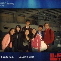 Image of UNRA-P3574-00085 - Color photograph of seven unidentified Upward Bound students posing in front of the U-505 submarine at the Museum of Science & Industry in Chicago. The submarine is a German U-boat captured by the U.S. Navy during World War II.