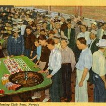 """Image of UNRS-P2017-01-00174 - Image of the interior of a gaming club in Reno, Nevada. The room is crowded with men. In the front left, there is a Roulette table with five participants watching. Caption on the Front: """"Interior of a Gaming Club, Reno, Nevada."""" Handwritten on Verso: """"Dear Virge, Am wondering if you are still in Berkley? We are coming home by way of Placerville this week. We will stop over there for a day and see the family. Bert was able to make enough to pay our expenses here this extra week, by putting in quite a lot of time at it. We have enjoyed our stay here. Love, Bert and Margaret."""" Addressed to Mrs. Virginia Laddish 3148 College Avenue, Berkeley California"""