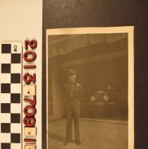Image of 2013.709.1.8 - A real photo postcard of a firefighter in front of the station house, Bell, California