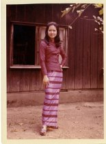 Image of A woman in a dress posing in front of a building, 1972