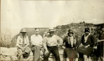 Image of Robert Turner (second from left) sitting with family on a rock wall, 1928
