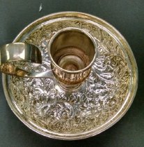 """Image of Sterling Silver Candlestick - A repousee-decorated sterling chamberstick or candlestick by Mauser Manufacturing Company that was originally doubled as the lid of a traveling desk set.  Monogramed on the underside with """"LTM""""."""