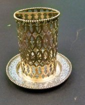 "Image of Silver Pencil Holder  ca 1915 - A sterling silver pencil holder marked J.E. Caldwell & Co. 440.   An open work cylinder soldered to a silver pattern, possibly custom assembled.  The open work tube is bisected at the top by a silver band thus dividing the cylinder into two sections.  The cylinder is numbered 102.  The pattern has a beaded edge and chased and engraved decoration with the monogram ""LMT"".   Weight is 1.92 troy oz."