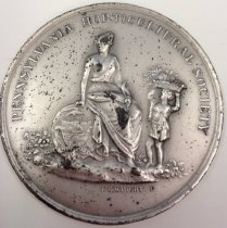 """Image of PHS Medal Awarded to Morris Arboretum   1940     - PHS silver medal awarded to Morris Arboretum Nov. 8, 1940    2"""" diameter. Unboxed. Front: Pennsylvania Horticultural Society surrounding a seated woman holding PA state seal with child holding harvest basket on head.  """"CC Wright"""" is embossed underneath.  (Charles Cushing Wright, die-caster, designer, d. 1854.) Back:  Harvest wreath surrounding engraved: Morris Arboretum, Swarthmore, PA, November 8, 1940"""