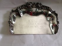 "Image of Adele West Tray  undated - Ceremonial silverplate tray shaped like a ""crumber""(dustpan shape).  With an upperedge border covering 3/4 of the item of stylized waves, flowers, leaves and curlicues.  Engraved:  ""In Memory of Adele R. West;  Wife, Mother, Friend. 