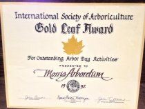 """Image of International Society of Arborculture, 1992 - International Society of Arboriculture,  """"Gold Leaf Award""""  For Outstanding Arbor Day Activities""""  Presented to Morris Arboretum, 1992;  applied gold seal of the """"IS of A"""". John Carson, Chapter President, Nancy Robin Morgan, Chair Arbor Day & Beautification Committee, John T. Moran, President of  """"IS of A"""". Commemorative certificate affixed to wood plaque.  Commemorative certificate affixed to wood plaque."""