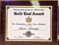 "Image of International Society of Arboriculture 1998 -  International Society of Arboriculture, ""Gold Leaf Award"" For Outstanding Arbor Day Activities"" Presented to Morris Arboretum,  applied gold & green seal IS of A"". For outstanding Arbor Day Activities. 1998.  Commemorative certificate affixed to wood plaque. 