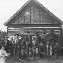 Image of 17 men, 1 woman, 1 girl in front of log cabin - Negative, Glass Plate