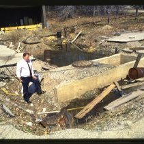 Image of Transparency, Slide - Mark Albrecht, Director of Campus Operations at Purchase College, standing at a hole where two 50,000 gallon oil tanks were removed after not passing inspection.  The hole was left empty due to budget cuts.  April 14, 1992
