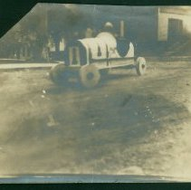 Image of Blurry childhood photo of Bill Milliken in wooden car