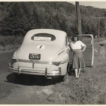Image of Wife of the official 1947 Glidden Tour photographer poses by their car.