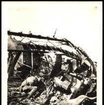 Image of Unidentified wrecked WWI airplane; soldier inspecting or casualty?