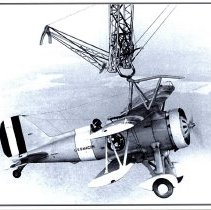 Image of Curtiss F9C Sparrowhawk with skyhook on exterior rigging of USS Macon ZRS-5